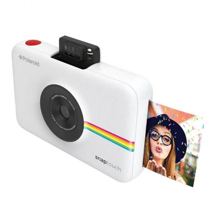 Tarrallisia valokuvia tulostava Polaroid-kamera ja runsas kuvausrekvisiitta.